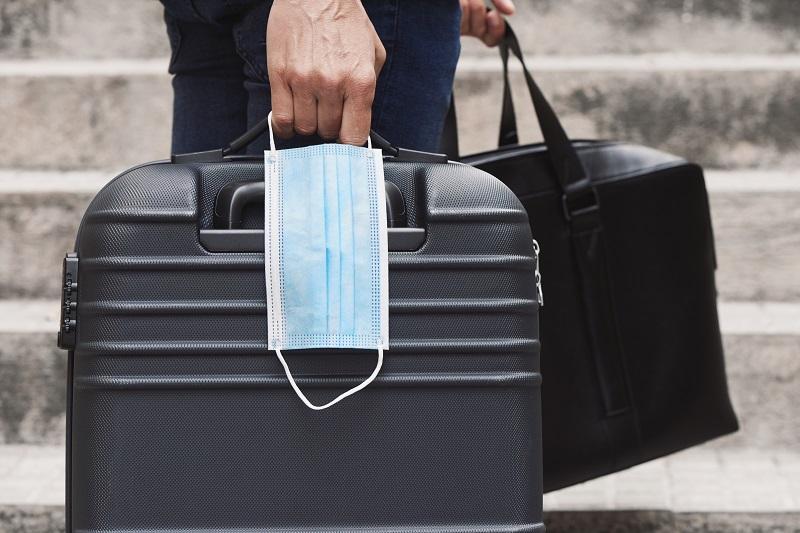 Business-Reisender hält Koffer, Tasche und Maske